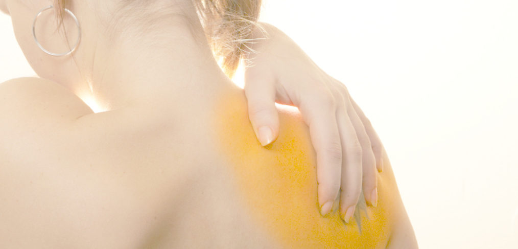 Photo showing the back of a woman with a sore shoulder. Her hand is on her shoulder.
